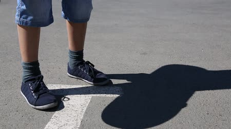 patim : Feet of boy riding a skateboard on the pavement.
