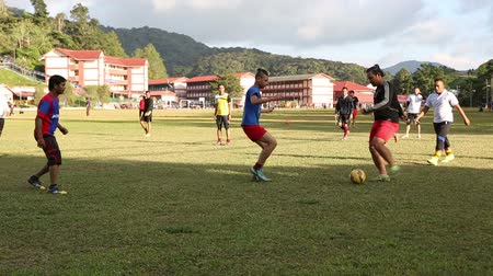 atleta : TANAH RATA, MALAYSIA - CIRCA FEBRUARY, 2015: Young guys playing soccer at the stadium in Tanah Rata, Cameron Highlands, Malaysia. Sports games are very popular among young people.