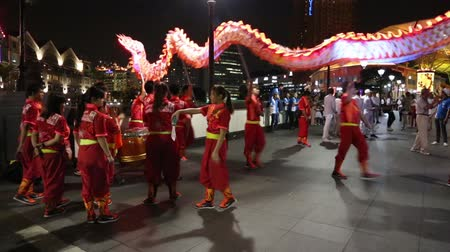 китайский новый год : SINGAPORE - JANUARY 26, 2015: Quay Singapore River is a very popular place with tourists and locals alike. Chinese people perform a dragon dance on the waterfront Singapore River.