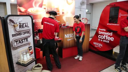 продукты : KUALA LUMPUR, MALAYSIA - JANUARY 31, 2015: Advertising campaign of a new kind of product Nescafe in a shopping center Kuala Lumpur. Employees offer to try a new kind of instant coffee. Стоковые видеозаписи
