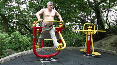 orta : Middleaged man doing wellness exercises on sports simulators in a city park in Macau.