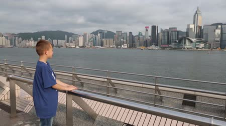 separação : HONG KONG CIRCA JUNE 2014: Boy is on the waterfront at the Kowloon Public Pier and looking at a panorama Hong Kong. Victoria Strait separates the island of Hong Kong and the mainland of Hong Kong.