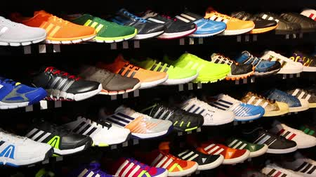 buty sportowe : HONG KONG CIRCA JUNE 2014: Showcase with shoes in Adidas store. Adidas AG is a German multinational corporation that designs and manufactures sports clothing and accessories in Germany Wideo