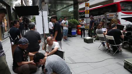 centrální čtvrť : HONG KONG CIRCA JUNE 2014: Working Group filmmakers with the equipment on the set. District Central is the business district of Hong Kong Island. Dostupné videozáznamy