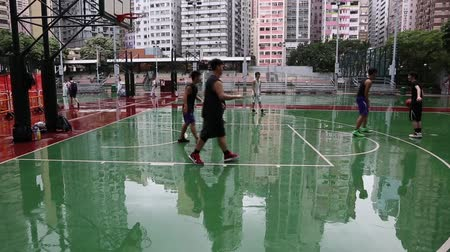juventude : HONG KONG CIRCA JUNE 2014: Young men playing street basketball after the rain. Youth enthusiastically engaged in collective sports games on the sports venues in the city. Vídeos