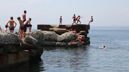 távozás : VLADIVOSTOK, RUSSIA - 22 JULY, 2015: Boy and girl jumping and diving into the sea from the old pier. Local children love to relax, sunbathe, swim and dive in Sports harbor Vladivostok.