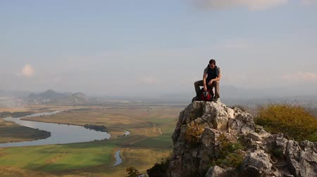 бутылки : Hiker man climbs to the top of the mountain by autumn morning. Panoramic view. At the top of drinking water from a bottle.