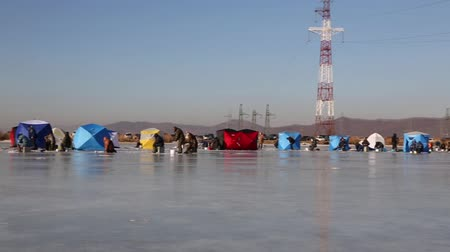 shishamo : Fishermen with tents on the ice of the river to catch smelt and saffron cod in the winter. December, temperatures -7 C. Primorsky Krai, Far East Russia. Stock Footage