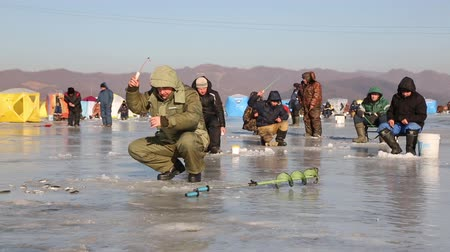shishamo : NAKHODKA, RUSSIA - DECEMBER 19, 2015: In winter, a lot of people catch fish from under the ice in the river Partizanskay. Fishing smelt and saffron cod is a popular activity among the local people.