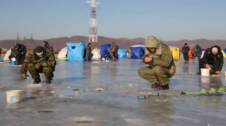 shishamo : NAKHODKA, RUSSIA - DECEMBER 19, 2015: In winter, people catch fish from under the ice in the river Partizanskay. Fishing smelt and saffron cod is a popular activity among the local people.