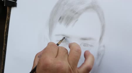 canvas : MOSCOW - CIRCA JUNE, 2016: Street artist paints a pencil a portrait of a boy on Arbat Street in Moscow. Stock Footage