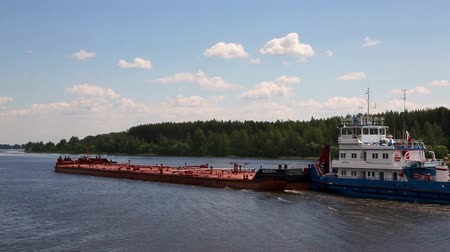 VOLGA RIVER, RUSSIA - CIRCA JUNE, 2016: Tug moves cargo barge on the Volga  river in the summer navigation.