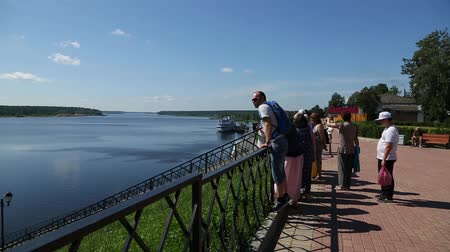 TUTAEV, RUSSIA - CIRCA JUNE, 2016: Tourists on the waterfront in the Tutaev city on the shores of Russian Volga River. Included in the tourist route Golden Ring of Russia