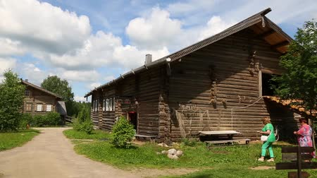 reconstructed : UPPER MANDROGI, RUSSIA - CIRCA JUNE, 2016: Tourists in the museum and the tourist village of Upper Mandrogi in Karelia. Restored houses in the Russian traditional style of the village street. Stock Footage