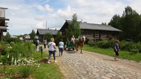 reconstructed : UPPER MANDROGI, RUSSIA - CIRCA JUNE, 2016: Tourists in the museum and tourist village of Upper Mandrogi in Karelia, north Russia. Restored houses in Russian traditional style of the village street