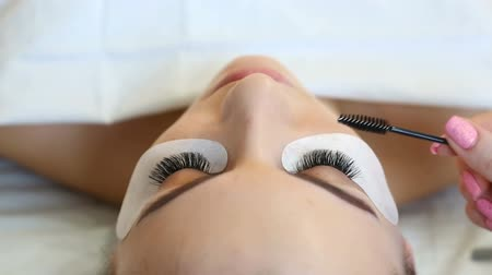 стегать : Eyelash Extension Procedure. Woman Eye with Long Eyelashes. Lashes, close up, selective focus. Стоковые видеозаписи