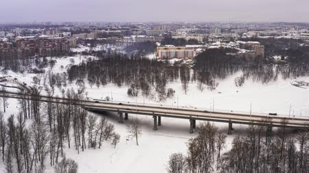 Snowy winter in beautiful city or town. Clip. Top view of frozen river, many cars on road, ancient buildings. Charming winter period in big city. Wonderful panorama Wideo