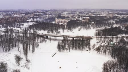 Snowy winter in beautiful city or town. Clip. Top view of frozen river, many cars on road, ancient buildings. Charming winter period in big city. Wonderful panorama Stock Footage