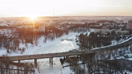 The bridge across the river winter. Span over the city with a bird. 4K Aerial. Over frozen city river and bridge in sunrise, sunset.