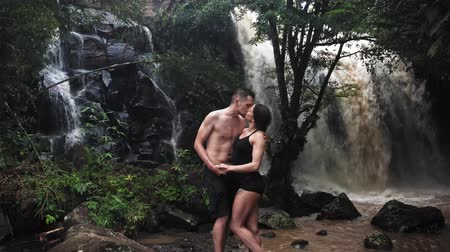 Couple hugging and kissing under a waterfall in a cave. A pair of lovers. Bali trip. Tropics. Journey. Aerial shot. Travel concept.