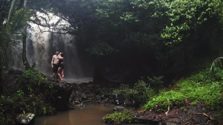 Couple in love under a waterfall in a cave. A pair of lovers. Bali trip. Tropics. Journey. Aerial shot. Travel concept.