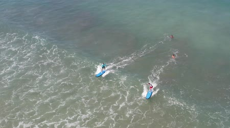 Two Beginners Surfing In Ocean Surf School. People surfing in the ocean of a beautiful beach Bali, Indonesia. Aerial view.