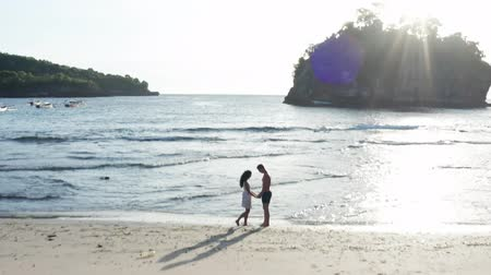 Man and Woman Walking Along Tropical Beach at Sunset, Tracking aerial shot of young couple on vacation having fun on the beach. Couple walking on empty beach at sunset by the beach.