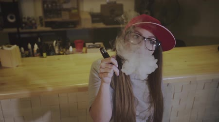 vaper : Young pretty woman in red cap smoke an electronic cigarette at the vape shop. Closeup. Slow motion.