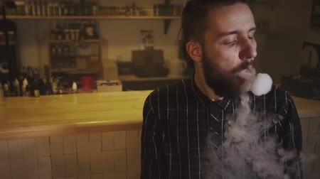 alışkanlık : The man smoke an electronic cigarette at the vape shop. Slow motion.