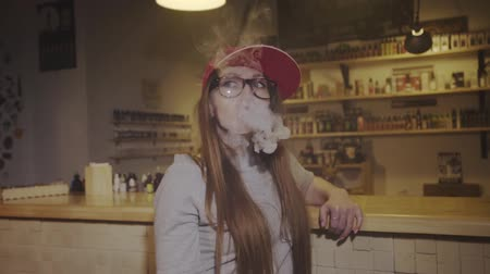 atomizer : Young pretty woman in red cap smoke an electronic cigarette at the vape shop. Closeup. Slow motion.