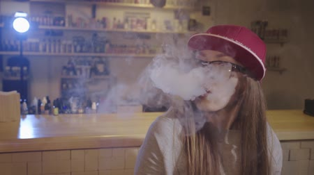 hiphop : Young pretty woman in red cap smoke an electronic cigarette at the vape shop. Closeup. Slow motion.