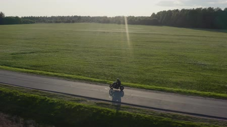 Man rides a motorcycle on a sunset country road Aerial dron tracking shot. 4K.