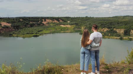 Couple is standing on a mountain cliff by the lake. Couple in love hugging against the background of beautiful views of nature. Aerial. 4K Stock Footage
