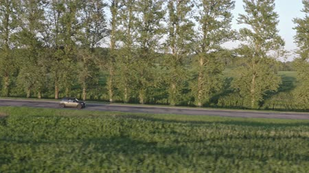 Aerial view of grey car driving on country road. Side view tracking shot. 4K.