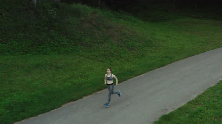 Young attractive girl running in city park. Woman running in wood aerial side view. 4K, tracking shot. Stock Footage