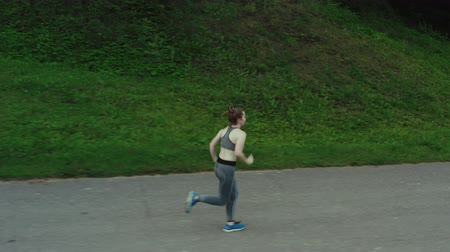 Young attractive girl running in city park. Woman running in wood aerial side view. 4K, tracking shot. Wideo