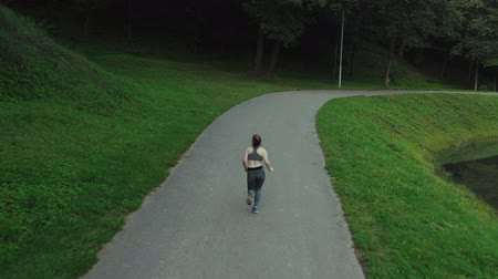 Young attractive girl running in city park. Woman running in wood aerial back view. 4K, tracking shot. Wideo