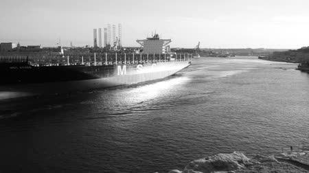 Мальта : VALLETTA, MALTA - MARCH 6, 2018: Huge empty container ship called MSC Athos exits Grand Harbour helped by tugboats at dusk. Time-lapse in black and white at the evening Стоковые видеозаписи