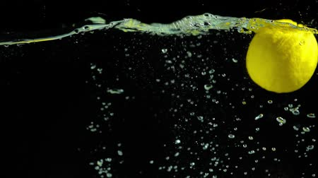 цитрусовые : bright green lemons falling into clear water on black background