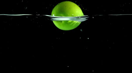 nutrientes : bright green apple falling into clear water on black background Vídeos