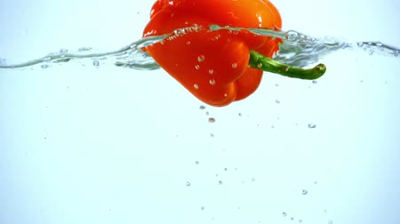 питательные вещества : bright orange bell pepper dipping in clear water on blue background with backlit