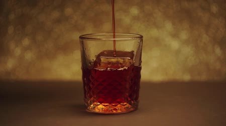 red square : Pouring into textured glass with big ice cube Stock Footage