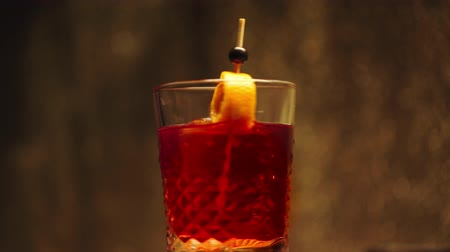 fogpiszkáló : toothpick with orange peel in spinning alcohol beverage on brown