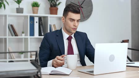 formální : Man drink coffee while sitting at workplace in office