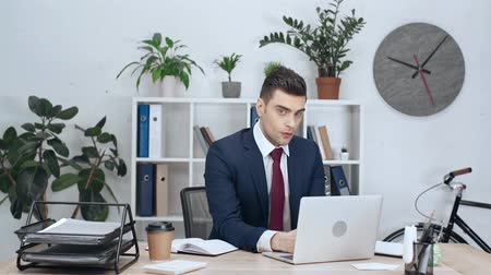 desgaste formal : handsome businessman sitting at workplace using laptop