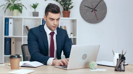 área de trabalho : attentive businessman using laptop while sitting at workplace