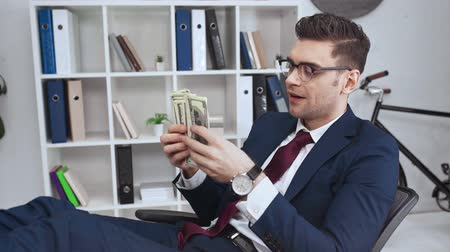 desgaste formal : happy successful businessman counting dollar banknotes in office