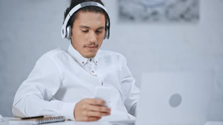 iyi seyir : handsome businessman in headphones and smartphone Stok Video