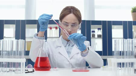 flasks : female scientist in goggles Stock Footage