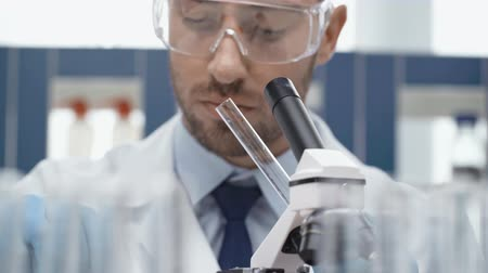 анализ : male scientist in goggles looking through microscope in laboratory Стоковые видеозаписи